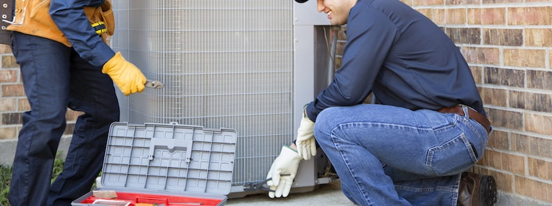 HVAC Technician installing outdoor HVAC unit